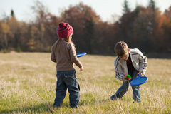 Kids playing tennis outside. Children playing tennis on the lawn in front of the forest Stock Photos