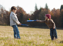 Kids playing tennis outside. Children playing tennis on the lawn in front of the forest Stock Image