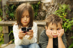 Kids playing to a cell phon Royalty Free Stock Photos