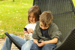 Kids playing to a cell phone Royalty Free Stock Image