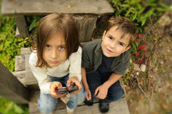 Kids playing to a cell phone Royalty Free Stock Images