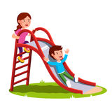 Kids playing together outside on the playground. School or preschool kids playing together outside on the kindergarten playground. Little boy sliding down the Royalty Free Stock Photos