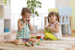 Kids playing with toy cubes in kindergarten room Stock Photos