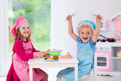 Kids playing with toy kitchen Royalty Free Stock Photo
