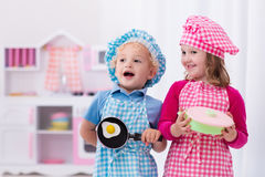 Kids playing with toy kitchen Stock Images