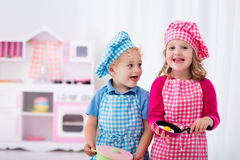Kids playing with toy kitchen Stock Photography