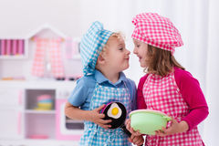 Kids playing with toy kitchen Stock Photo