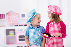 Kids playing with toy kitchen. Little girl and boy in chef hat and apron cooking fried eggs in toy kitchen. Wooden toys for young children. Kids play and cook at stock image