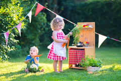 Kids playing with a toy kitchen in a summer garden Stock Images