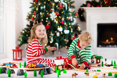 Kids playing with toy railroad on Christmas morning Royalty Free Stock Photography