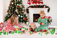 Kids playing with toy railroad on Christmas morning Stock Images