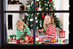 Kids playing with toy railroad on Christmas morning Royalty Free Stock Images