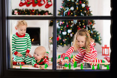 Kids playing with toy railroad on Christmas morning Stock Photo