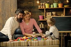 Kids playing with toys. Father, mother and cute son play with constructor bricks. Caring parents concept. Family on busy. Face spend time together in playroom Stock Photo