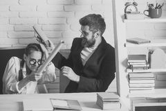 Kids playing with toys. Girl with glasses and bearded man fight with scrolls. Kids playing with toys. Girl with glasses and bearded men sit at desk and fight royalty free stock photography