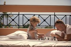 Kids playing with toys. Parent play chess with kid on terrace on sunny day. Father and little son play chess on balcony. Nature and sea on background. Dad with Stock Image
