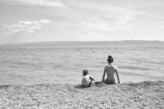 Kids playing with toys. mother and son on beach. Kids playing with toys. Rear view of mother and child in swimsuits sitting on beach of pebbles and looking at Royalty Free Stock Photo