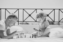 Smart toddler concept. Parent play chess with kid on terrace on sunny day. Kids playing with toys. Dad with child play. Kids playing with toys. Smart toddler royalty free stock photography
