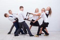 Kids playing tug of chair - girls versus boys Stock Photos