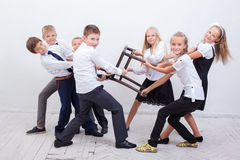 Kids playing tug of chair - girls versus boys Stock Photography