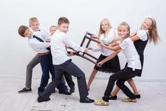 Kids playing tug of chair - girls versus boys Stock Photography