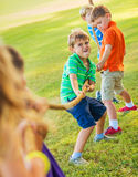 Kids playing Tug of War. Group of Happy Young Children Playing Tug oF War Outside on Grass Royalty Free Stock Image