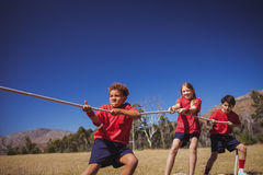Kids playing tug of war during obstacle course training Stock Image