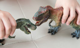 Kids playing two tyrannosaurus toys on a sofa Royalty Free Stock Photo