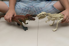Kids playing a tyrannosaurus toy and tyrannosaurus skeleton. On a sofa at home Stock Image