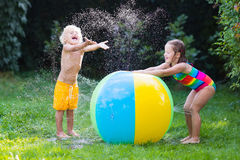 Kids playing with water ball toy. Child playing with toy ball garden sprinkler. Preschooler kid run and jump. Summer outdoor water fun in the backyard. Children Royalty Free Stock Photos