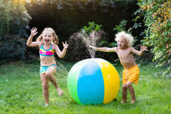 Kids playing with water ball toy sprinkler Stock Photos