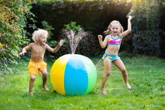 Kids playing with water ball toy sprinkler. Child playing with toy ball garden sprinkler. Preschooler kid run and jump. Summer outdoor water fun in the backyard Stock Photography