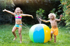 Kids playing with water ball toy sprinkler Royalty Free Stock Photo