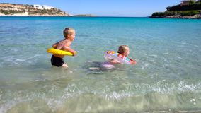 Kids playing in water at beautiful tropical beach. Kids playing in water at beautiful beach stock video footage