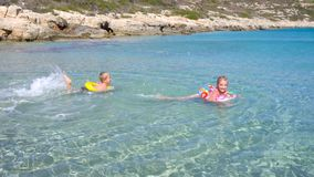 Kids playing in water at beautiful tropical beach. Kids playing in water at beautiful beach stock footage
