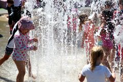 Kids playing in the water fountain in a hot day Stock Image