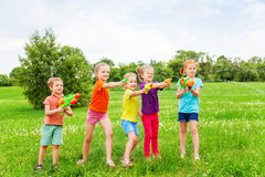 Kids playing with water guns on a meadow. Kids playing outdoors with water guns on a beautiful sunny day Stock Photo