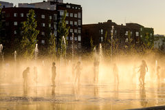 Kids playing with water. Silhouette of kids playing in with water/fountain at sunset Stock Image
