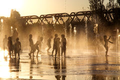 Kids playing with water. Silhouette of kids playing in with water/fountain at sunset Royalty Free Stock Photo