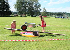 Kids playing with wheelbarrow on see-saw. Kids - barefoot girls in dresses playing with wheelbarrow on see-saw during firefighters competition (The 18th of June Stock Photo