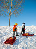 Kids playing in winter. Two kids playing outdoors for a day of winter sledding Stock Photos