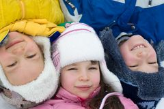 Kids Playing On a Winter Day. Three children lay on the snow on a cold winter day for this fun picture Stock Photos