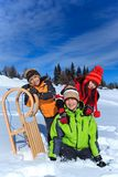 Kids playing in winter snow. Three happy children playing with a sled in winter snow Stock Images