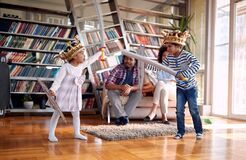 Free Kids Playing With Swords And Enjoying With Parents At Home. Family, Together, Love, Playtime Royalty Free Stock Photos - 212502058