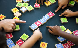 Kids playing wooden alphabets letters vocabulary ga stock photography