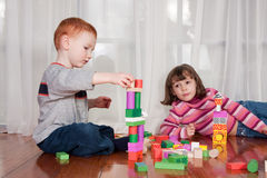 Kids playing with wooden blocks. Two kids playing with wooden blocks on polished floor with window behind Stock Photo