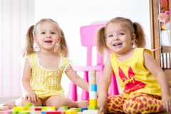 Kids playing with wooden blocks Stock Images