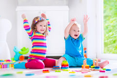 Kids playing with wooden blocks Stock Image