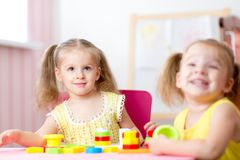 Kids playing with wooden blocks sitting at table Royalty Free Stock Photography