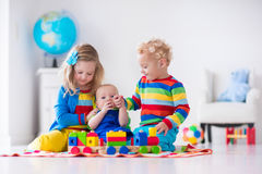 Kids playing with wooden toy train. Children playing with wooden train. Toddler kid and baby play with blocks, trains and cars. Educational toys for preschool Stock Image